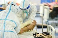 Workers prepare to transfer the body of a person who died from the Covid-19 coronavirus