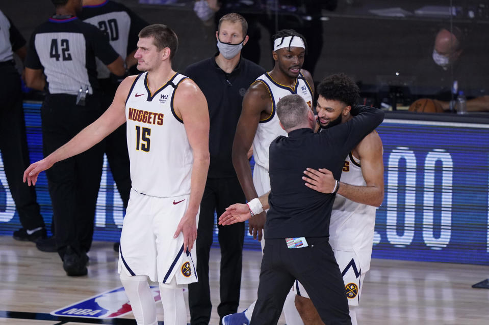 Denver Nuggets players and coaches celebrate their win over the Los Angeles Clippers in an NBA conference semifinal playoff basketball game Tuesday, Sept. 15, 2020, in Lake Buena Vista, Fla. (AP Photo/Mark J. Terrill)