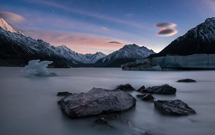 Tasman Glacier Lake in Mount Cook National Park Sunrise View with lenticular clouds.
