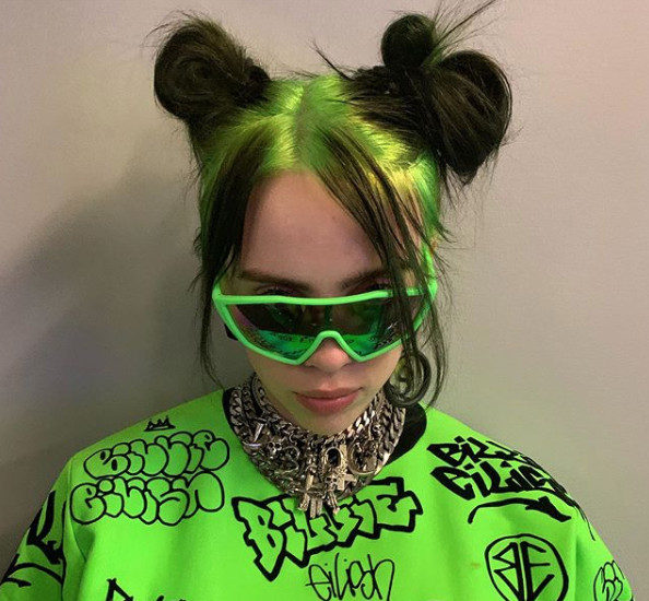 <p>Most people would totally be afraid to dye their roots neon green, but Billie went for it and the look didn't disappoint. She's paired the new dye job with several bright green outfits, like the top she's wearing here from her Freak City clothing collab. </p>