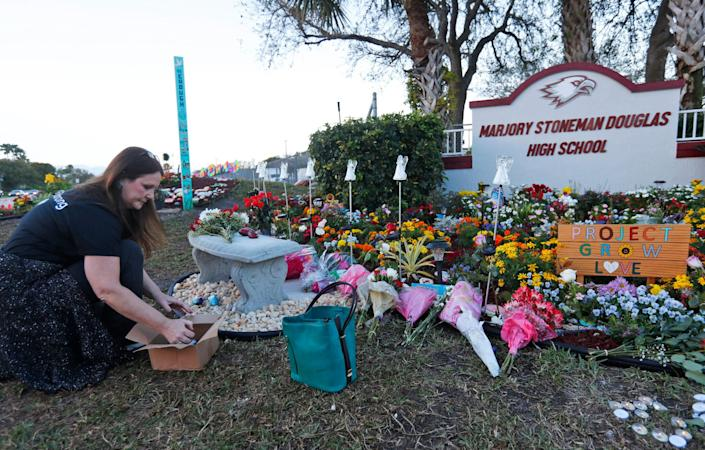 Suzanne Devine Clark, an art teacher at Deerfield Beach Elementary School, places painted stones at a memorial outside Marjory Stoneman Douglas High School during the first anniversary of the school shooting in 2019. (Photo: ASSOCIATED PRESS)