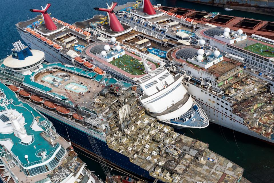 Aerial view from a drone, five luxury cruise ships are seen being broken down for scrap.
