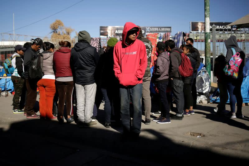 Mexican asylum seekers, who are camping near the Paso del Norte international border crossing bridge while waiting to apply for asylum to the U.S., gather outside their tents in Ciudad Juarez