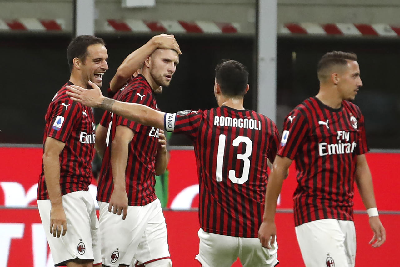 AC Milan's Ante Rebic, center left, celebrates with his teammates his goal against Juventus during the Serie A soccer match between AC Milan and Juventus at the San Siro stadium, in Milan, Italy, Tuesday, July 7, 2020. (AP Photo/Antonio Calanni)