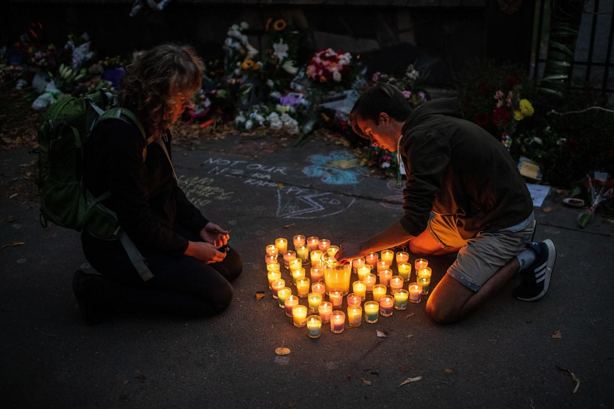 People light candles next to flowers and tributes laid by the wall of the Botanic Gardens on March 17, 2019 in Christchurch, New Zealand. (Photo: Carl Court/Getty Images)