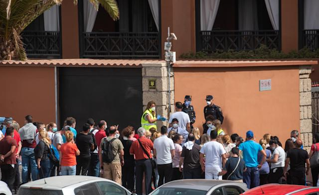 A psychologist talks to a group of workers outside the quarantined Tenerife hotel (Getty)