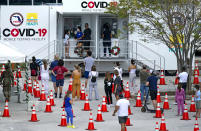 FILE - In this Nov. 18, 2020, file photo, people stand in line to being tested at the COVID-19 mobile testing facility at Miami Beach Convention Center in Miami Beach, Fla. With coronavirus cases surging and families hoping to gather safely for Thanksgiving, long lines to get tested have reappeared across the U.S. (David Santiago/Miami Herald via AP, File)