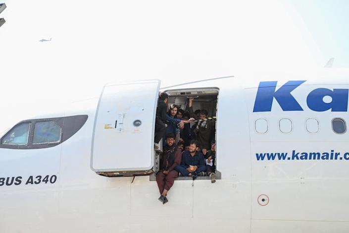 Afghan people climb up on a plane and sit by the door as they wait at the Kabul airport in Kabul on August 16, 2021. (Wakil Kohsar /AFP via Getty Images)