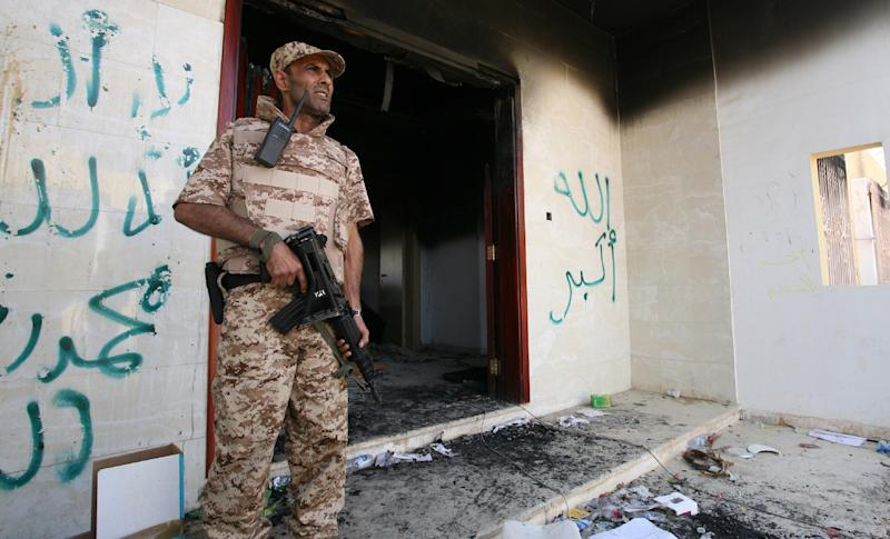 FILE - This Sept. 14, 2012 file photo shows a Libyan military guard standing in front of one of the U.S. Consulate's burnt out buildings during the visit of President Mohammed el-Megarif, not shown, to the U.S. Consulate, in Benghazi, Libya. Middle East violence is shaking up a U.S. presidential race that otherwise looks stubbornly stable _ and tight: President Barack Obama holds a tiny edge, Republican Mitt Romney seeks a break-through message, and three debates loom in the campaign's final seven weeks. Republicans and Democrats agree the election is likely to be decided on Obama's jobs-and-economy record, and both campaigns are entering a new campaign week working to shift the focus back to that issue. But foreign policy leaped to forefront of the campaign in recent days, as protestors attacked U.S. diplomats and missions in the Middle East. It's unclear when it will abate. (AP Photo/Mohammad Hannon)