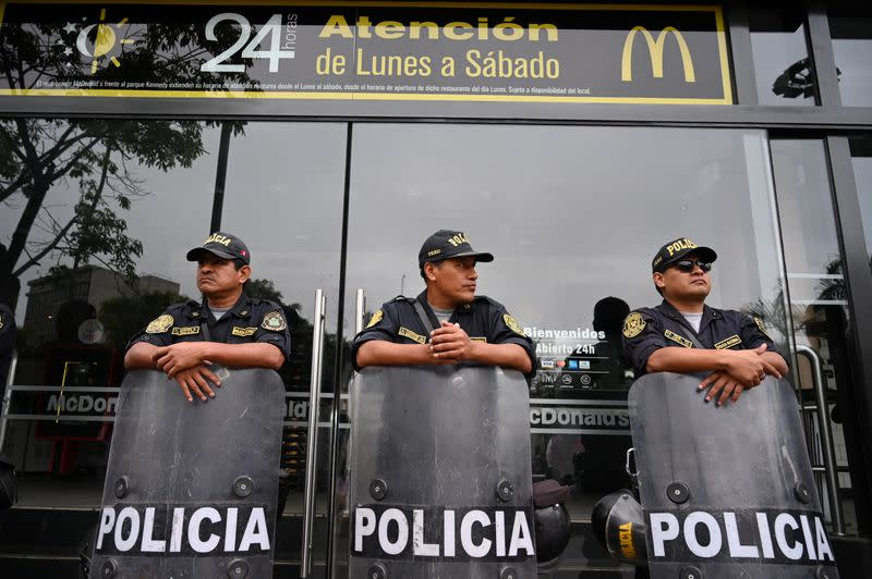 Police stand guard outside a closed McDonald's restaurant, during a protest after the deaths of two teenaged employees, in Lima