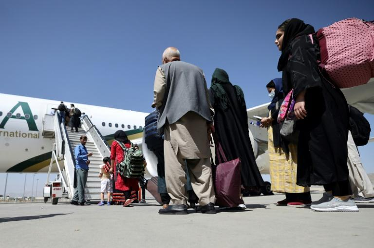 Passengers stand in a queue at Kabul airport to board a Pakistan International Airlines plane, the first international commercial flight to come in and out of the Afghan capital since the Taliban took over the country (AFP/Karim SAHIB)