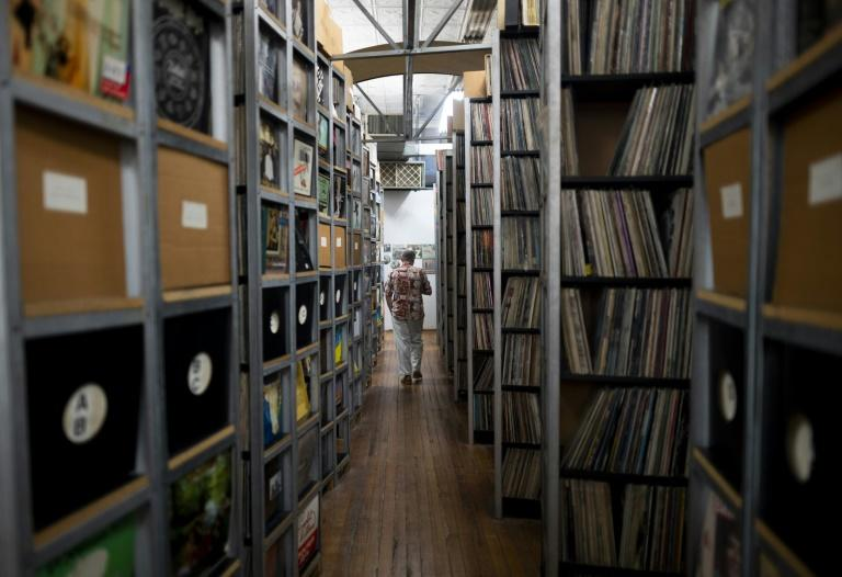 B. George, the Co-Founder and Director of the ARChive of Contemporary Music walks a corridor between the massive collection of records