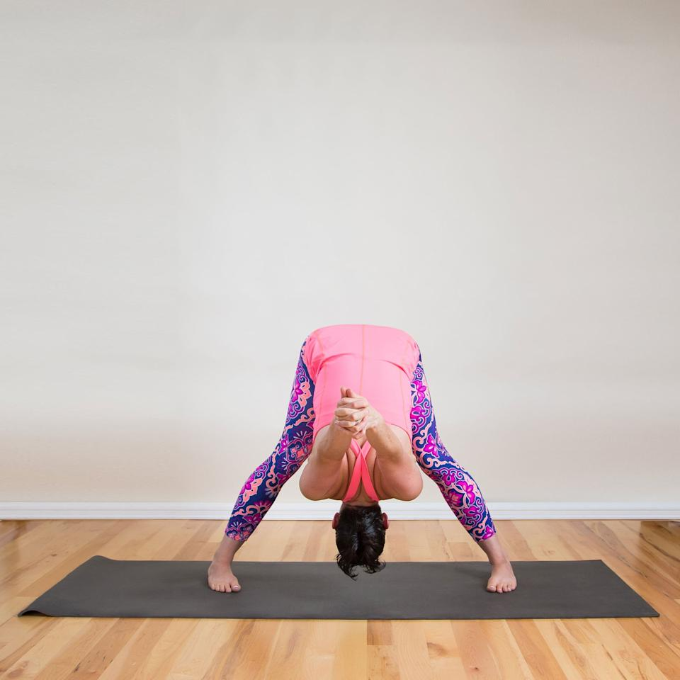 """<p>This stretch lengthens and tones the backs of your legs, often a tight area for many of us, said Michelle Thielen, founder of <a href=""""https://yogafaith.org/"""" target=""""_blank"""" class=""""ga-track"""" data-ga-category=""""Related"""" data-ga-label=""""https://yogafaith.org/"""" data-ga-action=""""In-Line Links"""">YogaFaith</a>. """"This pose can be invigorating and possibly replace your daily caffeine intake - it's that powerful!"""" Michelle told POPSUGAR.</p> <ul> <li>Stand with your feet three to four feet apart, placing your heels slightly wider than your toes.</li> <li>Bring your arms behind your back, clasping your fingers and pressing the heels of your palms together in a fist.</li> <li>Fold forward, hinging at your hips, drawing the crown of your head and your hands toward the floor. Relax your toes, and try to shift the weight of your hips forward so they're in line with your feet.</li> <li>Stay here for 10 deep breaths. Then press into your feet, engage your quads, and inhale as you stand up.</li> </ul>"""