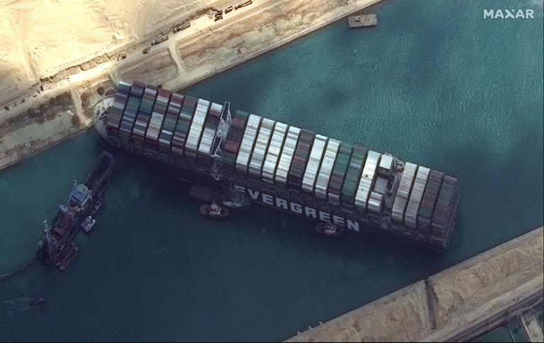 This satellite imagery released by Maxar Technologies shows tug boats and dredgers attempting to free the MV Ever Given on March 26, 2021, in the Suez Canal