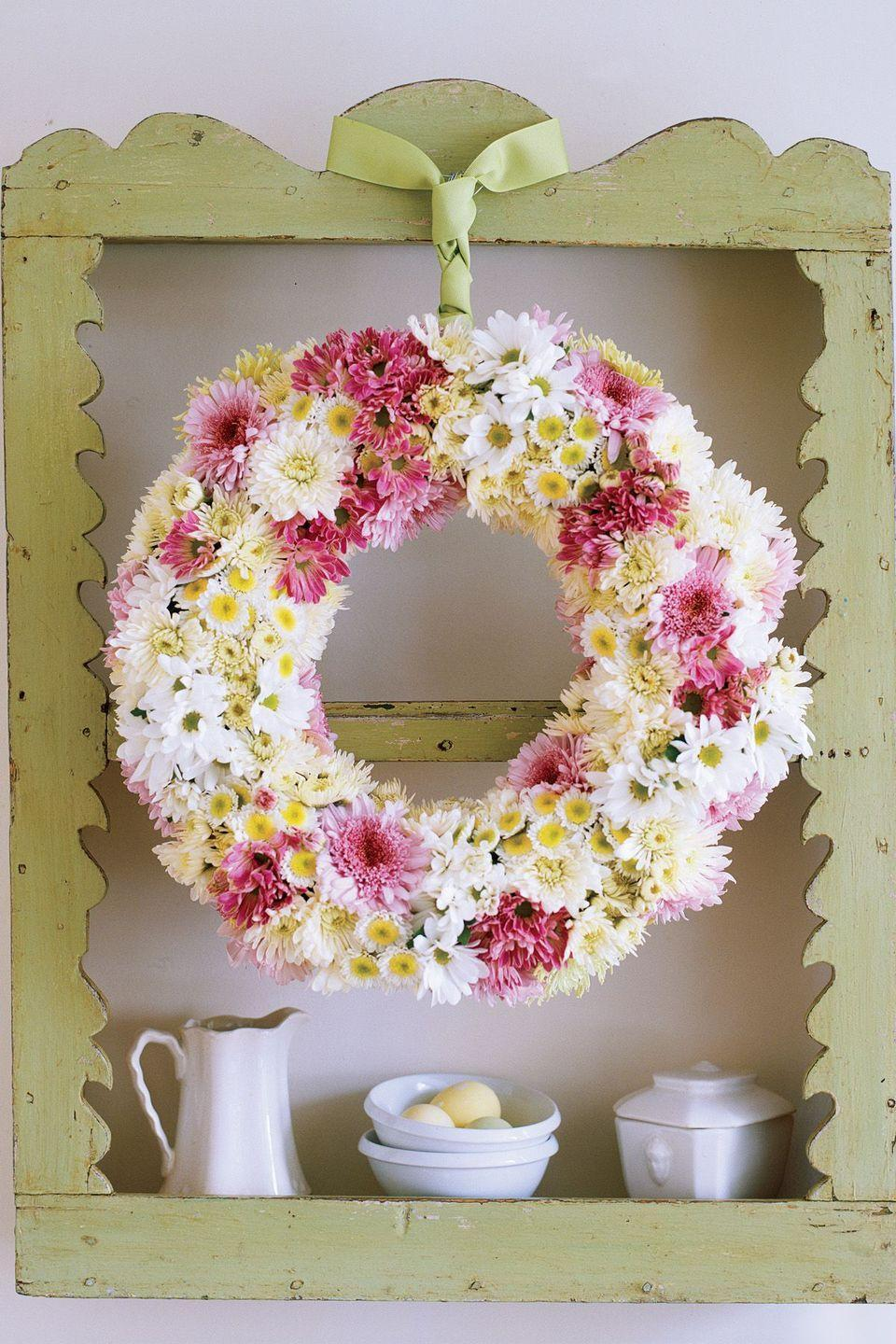 <p>This beauty is a wreath and floral arrangement all in one. To make your own garden-fresh wreath, dip a foam ring in water until it's damp but not dripping, then stand it upright in a sink for one hour to drain. Trim each flower stem to one to two inches, and insert into foam. Pack flowers tightly, overlapping them so no foam is visible. Add a wreath hook, wrap with ribbon, and finish with a dapper necktie knot. </p>
