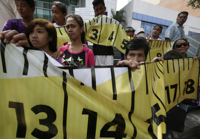 Protesters display a mock tape measure during a rally outside the Chinese consulate at the financial district of Makati city east of Manila, Philippines Wednesday, April 2, 2014. Dozens of Filipino left-wing activists protested at China's consulate to protest the blocking by Chinese coast guard ships of a Philippine supply boat near a disputed shoal in the South China Sea. (AP Photo/Bullit Marquez)