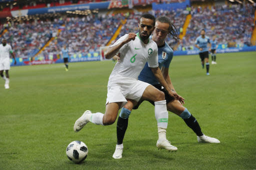 Uruguay's Diego Laxalt, right, and Saudi Arabia's Mohammed Alburayk challenge for the ball during for the group A match between Uruguay and Saudi Arabia at the 2018 soccer World Cup in Rostov Arena in Rostov-on-Don, Russia, Wednesday, June 20, 2018. (AP Photo/Darko Vojinovic)