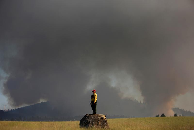 Marcus Johns with the Department of Natural Resources, watches as the Taylor Bridge Fire burns on the south side of Highway 970 near Swauk Prairie Road on Wednesday, Aug. 15, 2012 near Cle Elum, Wash. The Taylor Bridge Fire has forced hundreds to evacuate and has burned dozens of homes. (AP Photo/seattlepi.com, Joshua Trujillo)