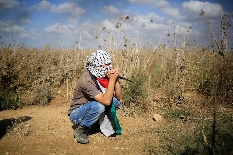 A Palestinian protester, holding a knife, looks on during clashes with Israeli security forces near the border fence between Israel and the Gaza Strip on October 9, 2015 (AFP Photo/Mohammed Abed)