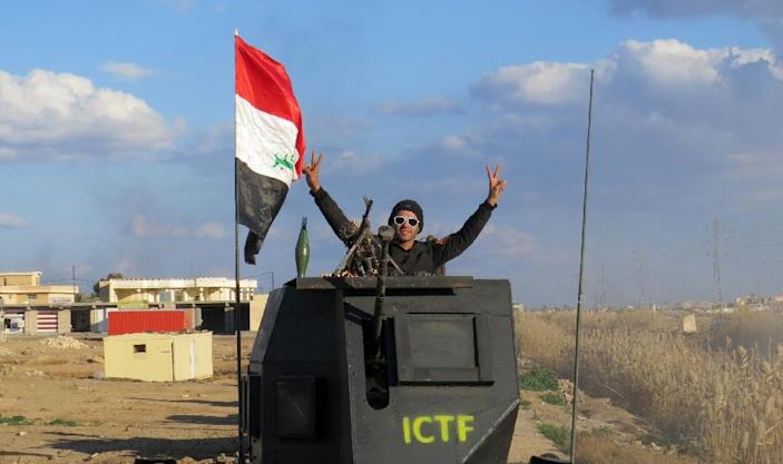 A member of Iraqi pro-governement forces flashes the sign of victory atop an armoured vehicle on February 8, 2016 in the Jwaibah area, on the eastern outskirts of Ramadi, after Iraqi troops retook it from Islamic State (IS) group jihadists (AFP Photo/Moadh Al-Dulaimi)