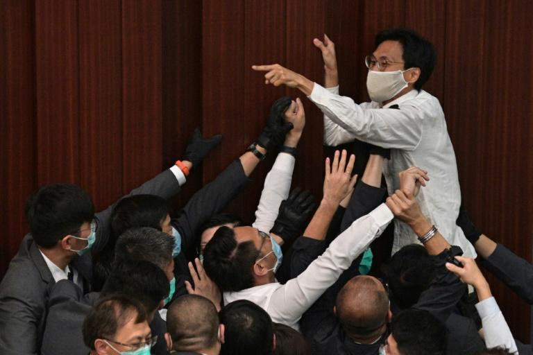 Hong Kong pro-democracy lawmaker Eddie Chu Hoi-dick shouts at security trying to restrain him after a pro-Beijing lawmaker sat in the chairperson's seat in a May 2020 skirmish that has prompted arrests by Chinese-aligned authorities