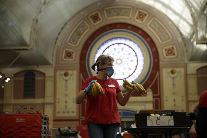 FILE - In this Tuesday, April 21, 2020 file photo, a volunteer for the Edible London food project checks and packs bananas to be put in food packs and delivered to residents who need it in the Haringey Council area, at a hub setup as a result of coronavirus inside the Alexandra Palace venue, in north London. A charity says U.K. food bank rose by a third during the past 12 months as the COVID-19 pandemic left more people without the money to buy basic necessities. The Trussell Trust said Thursday, April 22, 2021 that the food banks it works with handed out more than 2.5 million food parcels in the year through March, up from 1.9 million a year earlier. (AP Photo/Matt Dunham, File)