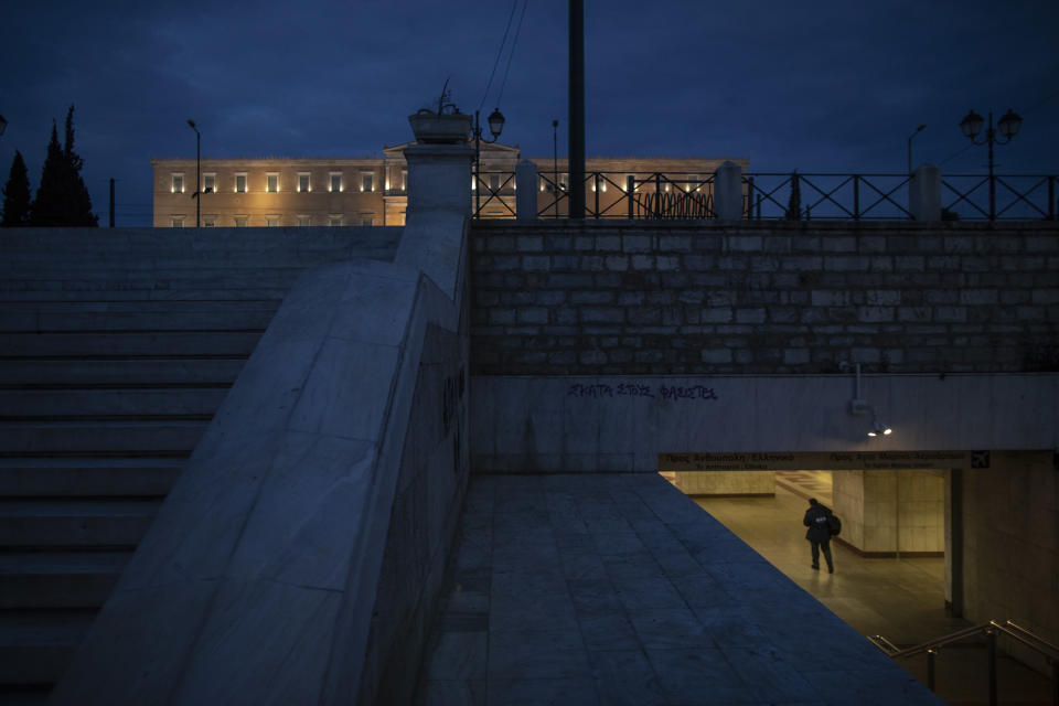 A man walks in Syntagma metro station, with the Greek Parliament building in the background, in central Athens, during lockdown to contain the coronavirus pandemic, on Wednesday, April 29, 2020 . Greek authorities say the use of face masks will be compulsory on pain of a 150-euro ($163) fine - in public transport and shops from May 4, when the country starts to ease its lockdown restrictions.(AP Photo/Petros Giannakouris)