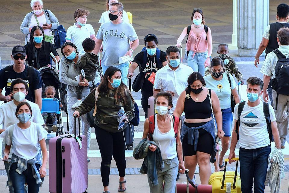 Travelers wearing protective face masks arrive at Orlando International Airport on the Friday before Memorial Day