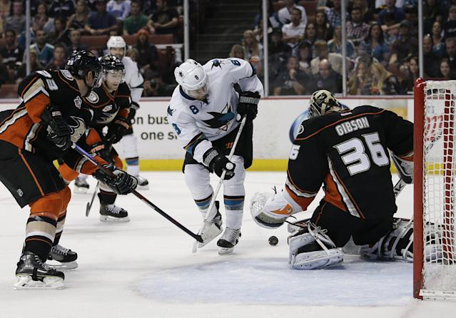 Anaheim Ducks goalie John Gibson, right, stops a shot by San Jose Sharks' Joe Pavelski, center, during the first period of an NHL hockey game Wednesday, April 9, 2014, in Anaheim, Calif. (AP Photo/Jae C. Hong)