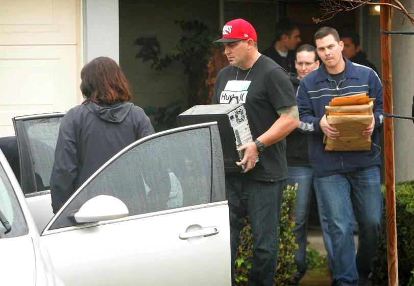 FBI and Homeland Security investigators carry a computer tower and manila envelopes from the Corona, Calif., home of Syed Raheel Farook while executing a search warrant at the home. F