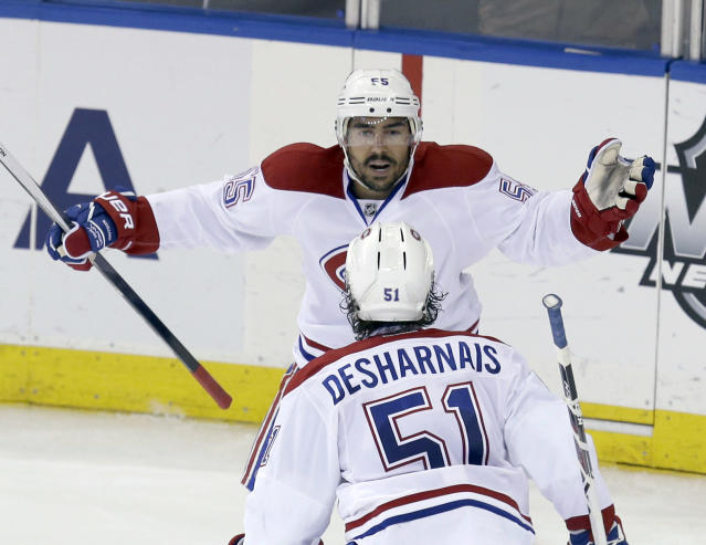 Montreal Canadiens' Francis Bouillon, top, celebrates with David Desharnais (51) after scoring during the second period of Game 4 of the NHL hockey Stanley Cup playoffs Eastern Conference finals against the New York Rangers, Sunday, May 25, 2014, in New York. (AP Photo/Seth Wenig)