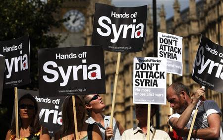 Demonstrators hold placards outside the Houses of Parliament in London in this August 29, 2013 file picture. REUTERS/Suzanne Plunkett