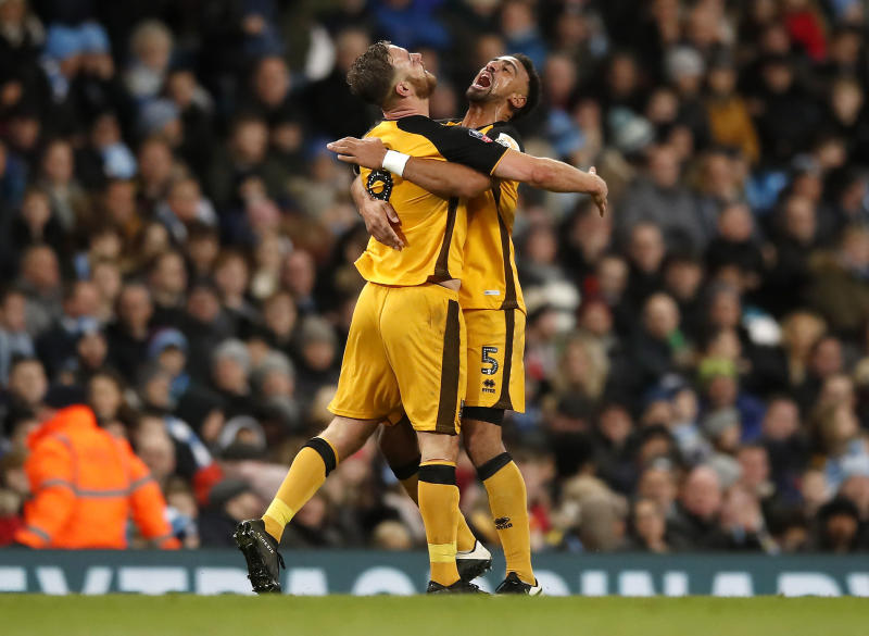 Port Vale's Tom Pope, left, celebrates scoring his side's first goal of the game with teammate Leon Legge during the English FA Cup third round soccer match between Manchester City and Port Vale at the Etihad Stadium, Manchester, England, Saturday, Jan. 4, 2020. (Martin Rickett/PA via AP)