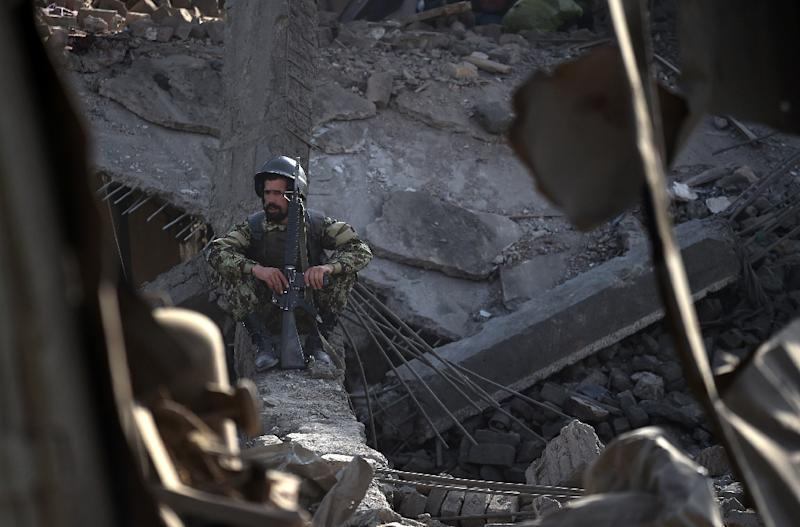 An Afghan National Army soldier sits inside a damaged building after a powerful truck bomb explosion in Kabul on August 7, 2015 (AFP Photo/Wakil Kohsar)