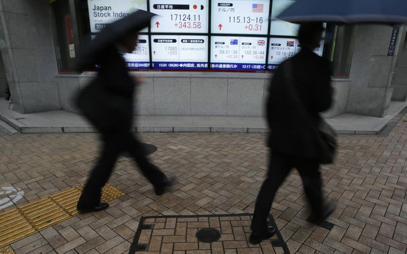 Pedestrians with umbrellas walk past an electronic board showing Japan's Nikkei average and the exchange rates between the Japanese yen and the U.S. dollar, outside a brokerage in Tokyo