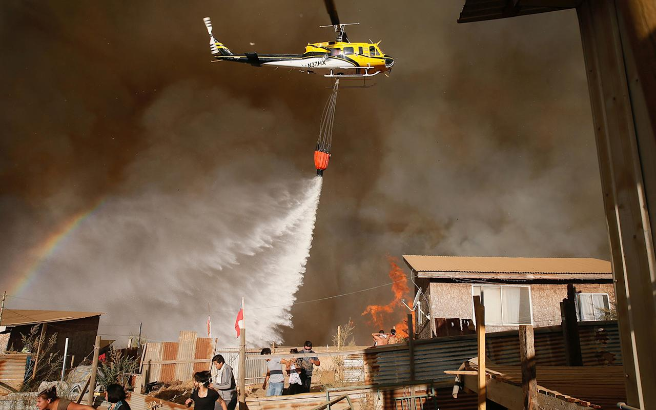 <p>A helicopter makes a water drop to prevent a wildfire from spreading to homes in Vina del Mar, Chile March 12, 2017. (Photo: Rodrigo Garrido/Reuters) </p>