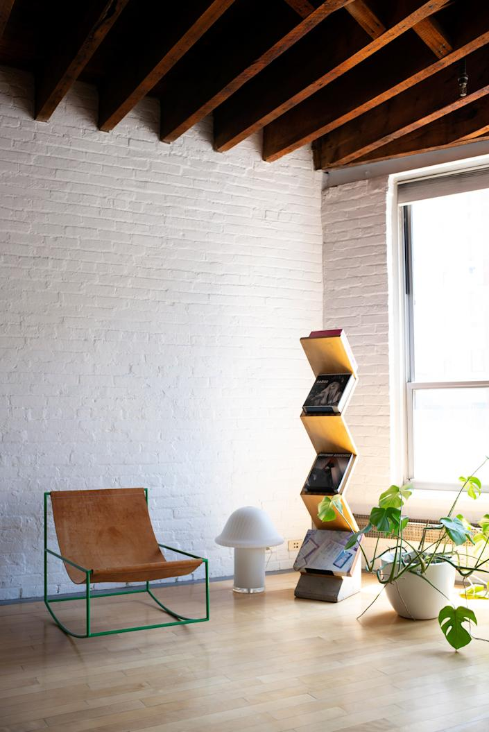 """<div class=""""caption""""> One corner of the loft is decorated with a <a href=""""https://mattermatters.com/collections/muller-van-severen-1/products/first-rocking-chair"""" rel=""""nofollow noopener"""" target=""""_blank"""" data-ylk=""""slk:Muller van Severen rocking chair"""" class=""""link rapid-noclick-resp"""">Muller van Severen rocking chair</a> from Matter, a mushroom-shaped lamp from <a href=""""https://comingsoonnewyork.com/"""" rel=""""nofollow noopener"""" target=""""_blank"""" data-ylk=""""slk:Coming Soon"""" class=""""link rapid-noclick-resp"""">Coming Soon</a>, and a Zink bookshelf by <a href=""""https://www.suiteny.com/product/detail/workspace-storage-organization/zink-2166"""" rel=""""nofollow noopener"""" target=""""_blank"""" data-ylk=""""slk:Jonas Bohlin for Källemo"""" class=""""link rapid-noclick-resp"""">Jonas Bohlin for Källemo</a>. </div>"""