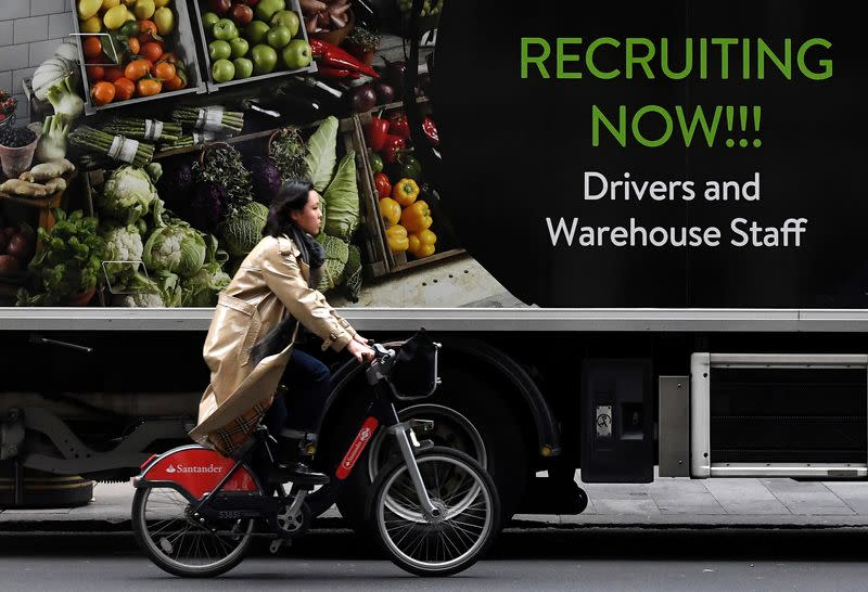 Cyclist rides past a sign on the side of a delivery lorry advertising for jobs, in London