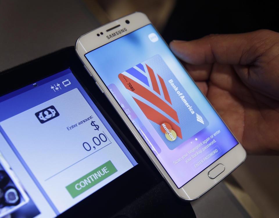 FILE - In this Aug. 6. 2015, file photo, a Samsung employee demonstrates Samsung Pay using a Galaxy S6 Edge Plus in New York. Mobile wallets come in different digital forms. There are device specific platforms, such as Apple Pay and Samsung Pay, which are compatible with Apple and Samsung devices, respectively. Google Pay works with multiple platforms, including Android devices. (AP Photo/Seth Wenig, File)