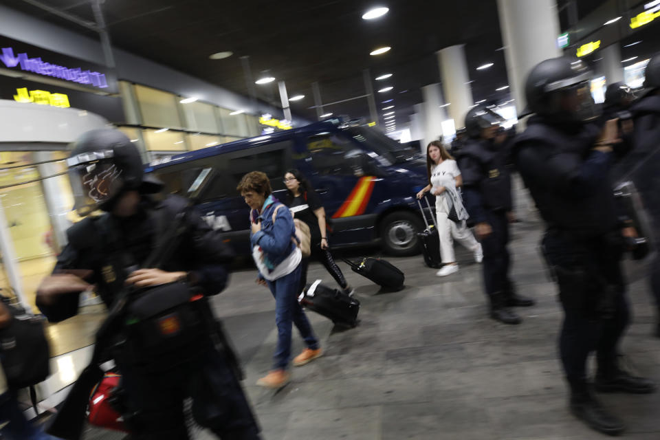 Passengers walk past a line of riot police standing on the way of protestors outside El Prat airport in Barcelona, Spain, Monday, Oct. 14, 2019. Spain's Supreme Court on Monday convicted 12 former Catalan politicians and activists for their roles in a secession bid in 2017, a ruling that immediately inflamed independence supporters in the wealthy northeastern region. (AP Photo/Emilio Morenatti)