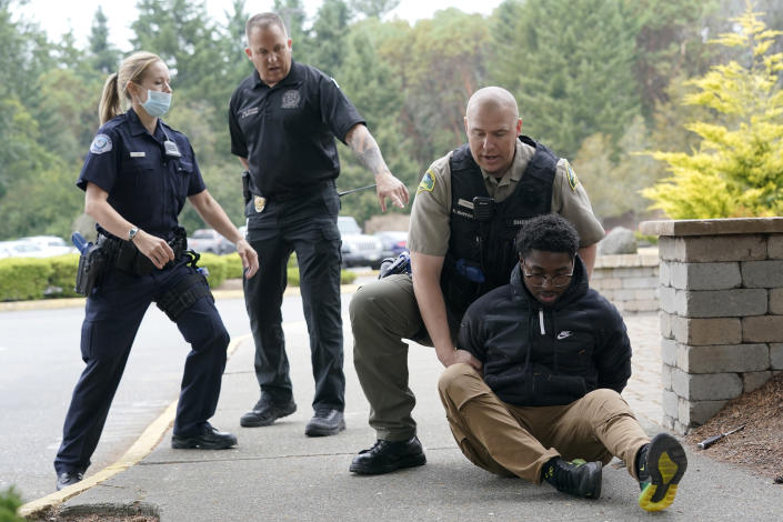 Kevin Burton-Crow, upper-right, of the Thurston Co. Sheriff's Dept., handcuffs Naseem Coaxum, right, an actor playing the role of a person causing a disturbance at a convenience store, during a training class at the Washington state Criminal Justice Training Commission, Wednesday, July 14, 2021, in Burien, Wash., instructor Ken Westphal, second from left, an officer with the Lacey Police Dept., and LeAnne Cone, left, of the Vancouver Police Dept., look on. Washington state is embarking on a massive experiment in police reform and accountability following the racial justice protests that erupted after George Floyd's murder last year, with nearly a dozen new laws that took effect Sunday, July 25 but law enforcement officials remain uncertain about what they require in how officers might respond — or not respond — to certain situations, including active crime scenes and mental health crises. (AP Photo/Ted S. Warren)