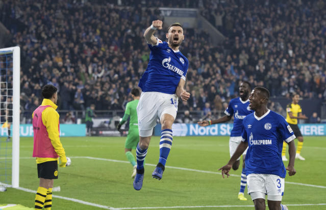 Schalke's Daniel Caligiuri , front, celebrates after scoring his side's first goal in the German Bundesliga soccer match between FC Schalke 04 and Borussia Dortmund in Gelsenkirchen, western Germany, Saturday, Dec. 8, 2018. (Bernd Thissen/dpa via AP)