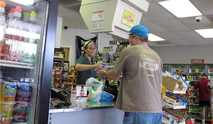 Store clerk Sierra Allison completes a transaction with a customer at the Lake Wylie Minimart in Lake Wylie, S.C. on Wednesday, March 21, 2012. The store's owner thought his business was in South Carolina, but surveyors have determined it is actually in North Carolina, meaning his gas prices will likely go up 30 cents and he can't sell fireworks. (AP Photo/Jeffrey Collins)