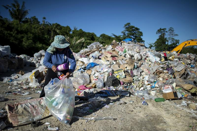 Gina Galan, 45, collects plastic bottles on the Boracay dumpsite in the Philippine island of Boracay on April 25, 2018.