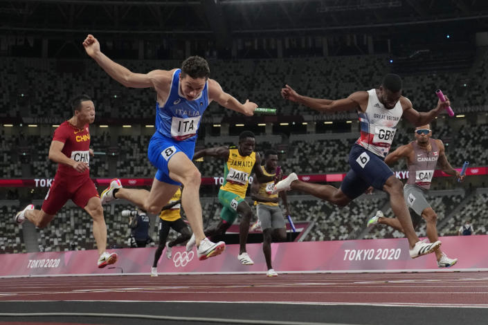Filippo Tortu, of Italy, crosses the finish line ahead of Nethaneel Mitchell-Blake, of Britain, to lead his to team a gold medal in the men's 4x100-meter relay at the 2020 Summer Olympics, Friday, Aug. 6, 2021, in Tokyo. (AP Photo/David J. Phillip)