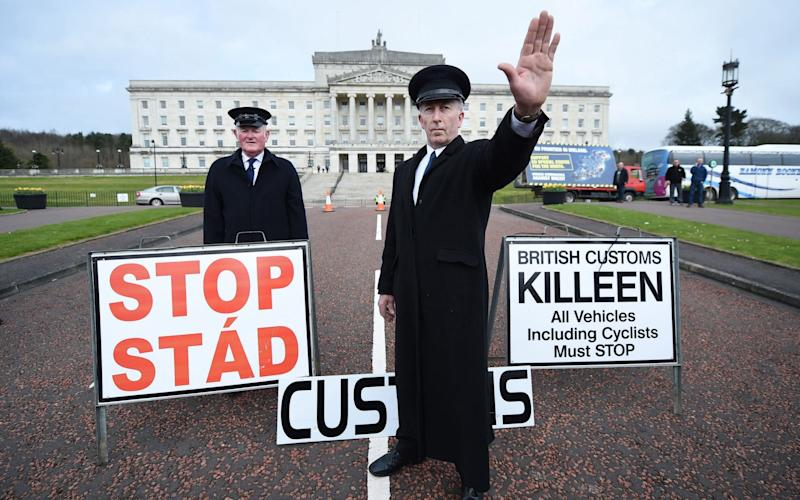 Two men dressed as customs officers take part in a protest outside Stormont against Brexit and its possible effect on the north and south Irish border - Getty Images Europe
