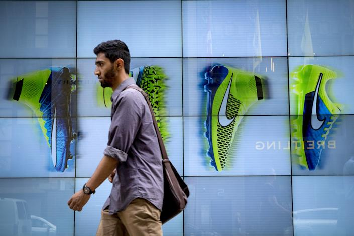 A man passes by the Niketown store in midtown Manhattan in New York June 25, 2015. Nike Inc, the world's largest footwear maker, reported a better-than-expected profit for the eighth quarter in a row as it sold more high margin basketball shoes and apparel at higher prices.  REUTERS/Brendan McDermid