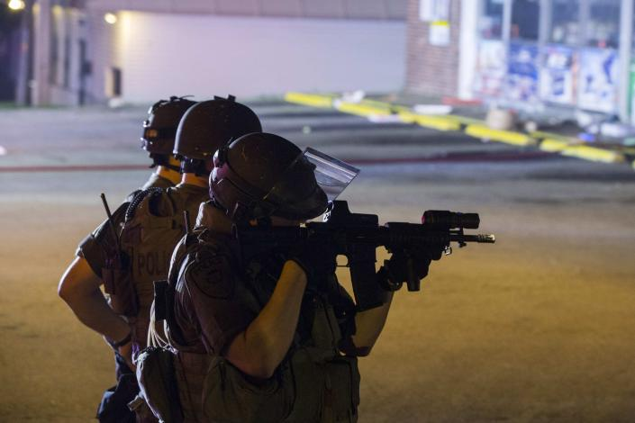 Police officers react at the scene of a looting at the Dellwood Market after protests against the shooting of Michael Brown turned violent near Ferguson, Missouri August 17, 2014. Shots were fired and police shouted through bullhorns for protesters to disperse, witnesses said, as chaos erupted Sunday night in Ferguson, Missouri, which has been racked by protests since the unarmed black teenager was shot by police last week. REUTERS/Lucas Jackson (UNITED STATES - Tags: CIVIL UNREST CRIME LAW)