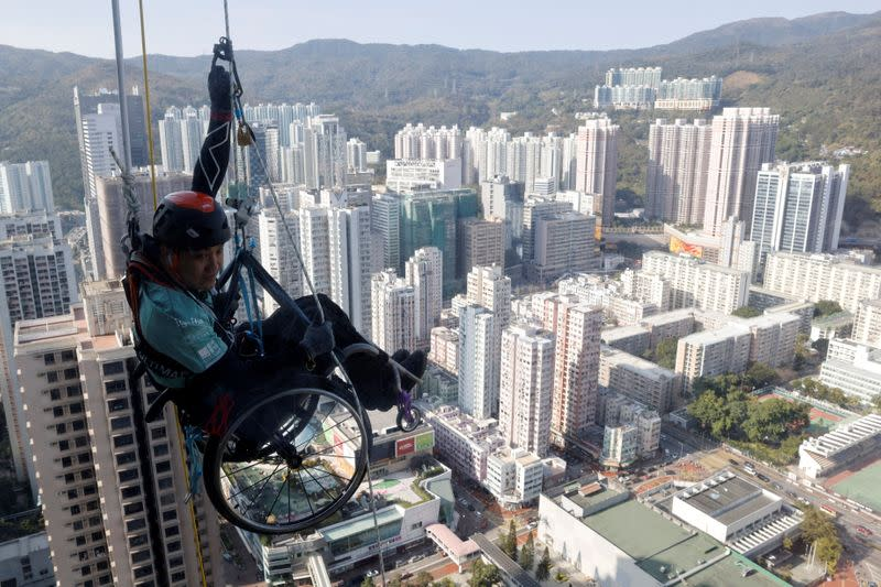 Lai Chi-wai, a paraplegic climber, attempts to climb the 320-metre tall Nina Tower using only his upper body strength in Hong Kong