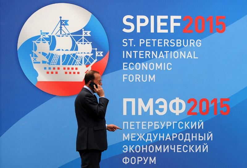A man talks on the phone in front of a banner bearing the logo of the St Petersburg International Economic Forum on June 18, 2015 in Russia (AFP Photo/Olga Maltseva)